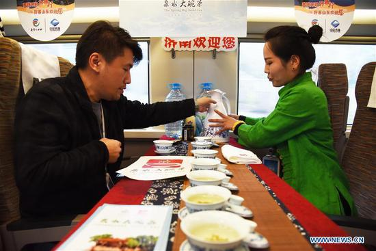 A passenger experiences the tea culture of Jinan on a tourism experience train in east China's Shandong Province, Nov. 24, 2019. A tourism experience train of high-speed rail line circling eight cities of Shandong Province started its journey from Jinan West Railway Station to the other cities, including Linyi, Rizhao and Qingdao, on Sunday, with specialties of the eight cities on display on the train. (Xinhua/Wang Kai)