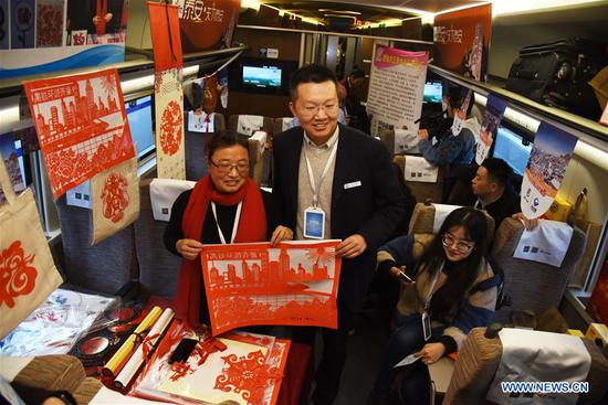A passenger (1st L) poses for a photo with a paper-cutting artist from Taian on a tourism experience train in east China's Shandong Province, Nov. 24, 2019. A tourism experience train of high-speed rail line circling eight cities of Shandong Province started its journey from Jinan West Railway Station to the other cities, including Linyi, Rizhao and Qingdao, on Sunday, with specialties of the eight cities on display on the train. (Xinhua/Wang Kai)