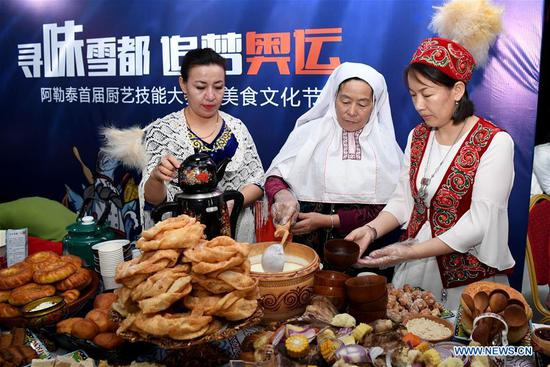 Women of Kazakh ethnic group show their traditional food in Altay, northwest China's Xinjiang Uygur Autonomous Region, Nov. 27, 2019. The 14th Xinjiang Winter Tourism Trade Fair opened here on Wednesday. (Xinhua/Sadat)