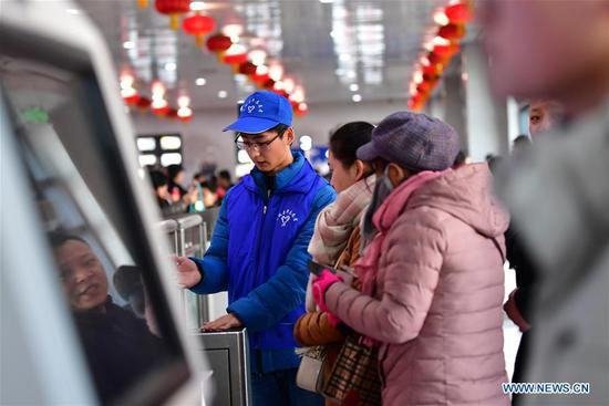A volunteer helps passengers get through the automatic entry gate at Lanzhou Railway Station in Lanzhou, capital of northwest China's Gansu Province, Jan. 13, 2020. During the Spring Festival travel rush, Lanzhou Railway Station and Lanzhou West Railway Station roll out a special voluntary service named