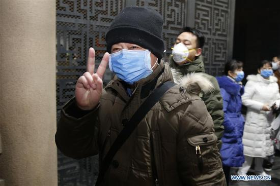 A medical team member from Anzhen Hospital flashes the victory sign before leaving for Wuhan of Hubei Province, in Beijing, capital of China, Jan. 27, 2020. A team comprised of 136 medical workers from Beijing left for Wuhan City on Monday to aid the novel coronavirus control efforts there. (Xinhua/Zhang Yuwei)