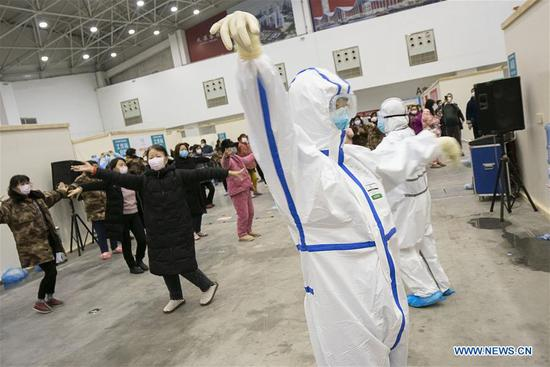 Patients do exercise led by medical staff at a temporary hospital converted from