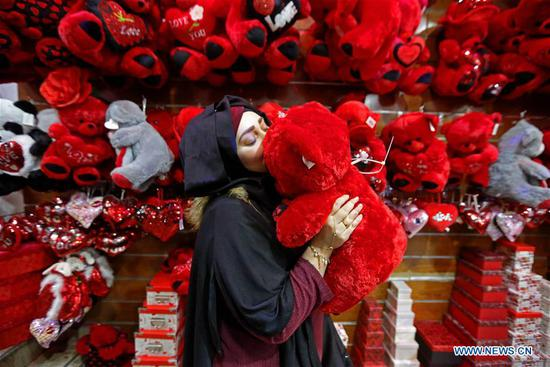 A woman selects a gift for the Valentine's day at a market in Beirut, Lebanon, Feb. 13, 2020. (Photo by Bilal Jawich/Xinhua)