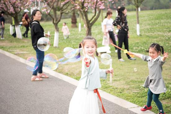 Children have fun at the wetland park of Fenghuang Lake in Chengdu, capital of southwest China's Sichuan Province, March 25, 2020. (Xinhua/Xu Bingjie)