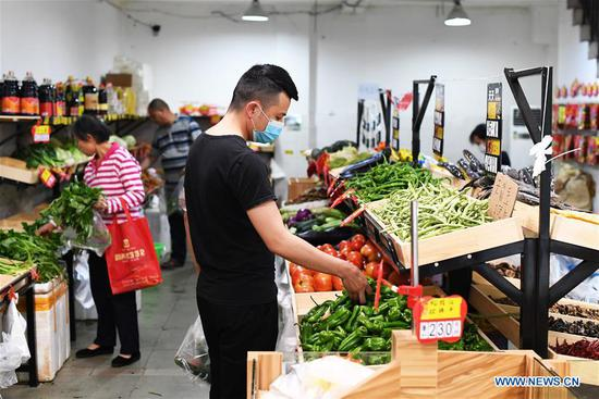 People buy vegetables at a store in Yubei District of southwest China's Chongqing Municipality on May 12, 2020. China's consumer price index (CPI) grew 3.3 percent year on year in April, moderating from the 4.3-percent gain in March, according to data from the National Bureau of Statistics (NBS). (Xinhua/Wang Quanchao)