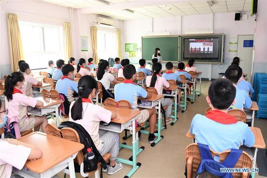 Students watch a video named the first class of this semester at a classroom in Shuangyushu No. 1 Primary School in Beijing, capital of China, June 1, 2020. Students at their first and second grades of senior high schools, first and second grades of junior high schools and sixth grade of primary schools returned to school for this semester in Beijing on Monday. (Xinhua/Ren Chao)
