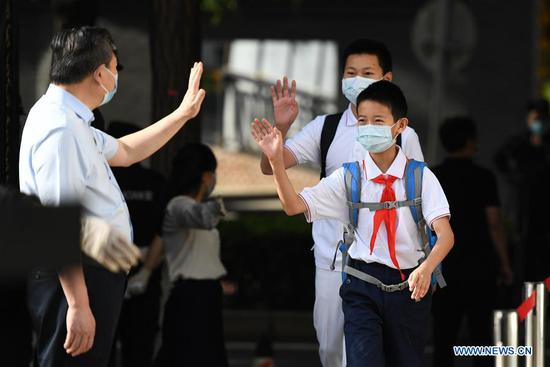 Students greet a teacher when entering the school in Beijing, capital of China, June 1, 2020. Students at their first and second grades of senior high schools, first and second grades of junior high schools and sixth grade of primary schools returned to school for this semester in Beijing on Monday. (Xinhua/Ju Huanzong)