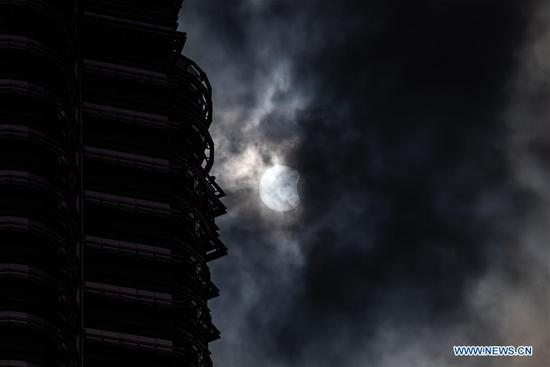 A partial solar eclipse is seen near the Petronas Twin Towers in Kuala Lumpur, Malaysia, on June 21, 2020. (Xinhua/Zhu Wei)
