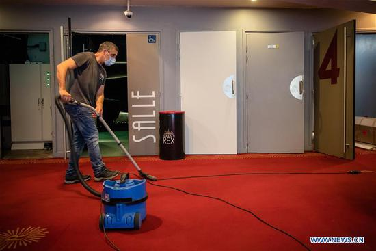 A worker uses a vacuum cleaner during preparations for the reopening of Le Grand Rex cinema in Paris, France on June 22, 2020. France, which gradually eased national lockdown from May 11, entered a new phase of de-confinement on Monday. Cinemas and casinos resumed activities and sports event attracting no more than 5,000 people would be allowed. (Photo by Aurelien Morissard/Xinhua)