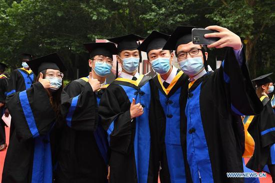 Graduates pose for a photo after the commencement ceremony at Beihang University in Beijing, capital of China, June 29, 2020. Beihang University held a commencement ceremony for the Class of 2020 (Bachelor's Degrees) on Monday. In order to reduce the risk of infection of COVID-19, only a minority of graduates attended the ceremony on site with the others attending online. (Xinhua/Ren Chao)