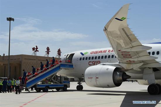 Staff members of a C919 large passenger aircraft disembark from the plane at the Turpan Jiaohe Airport in Turpan, northwest China's Xinjiang Uygur Autonomous Region, June 28, 2020. China's indigenously-developed C919 large passenger aircraft has started high-temperature test flights in Turpan, a city known as the land of fire in northwest China's Xinjiang Uygur Autonomous Region. The C919 conducted a successful maiden flight in 2017. Now the aircraft has started intensive test flights from various airports to make sure performance can meet airworthiness standards. (Photo by Liu Jian/Xinhua)