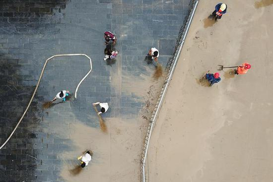 Workers clean up mud-covered roads after flood recedes in Jishou City, C China