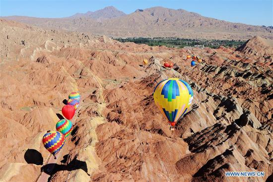 Hot air balloons are seen in the sky at Danxia National Geological Park in Zhangye, northwest China's Gansu Province, July 26, 2020. An international hot air balloons festival opened here on Sunday. A total of 100 hot air balloons will bring performances during the festival. (Photo by Cheng Lin/Xinhua)