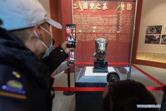 Visitors take photos of a bronze horse head sculpture looted from Yuanmingyuan which is on display at Wenshu Pavilion of Zhengjue Temple in Yuanmingyuan, Beijing, capital of China, Dec. 1, 2020. A bronze horse head sculpture, a treasure of China's Old Summer Palace that went missing after an Anglo-French allied forces' looting 160 years ago, returned to its original palace home Tuesday. It is the first time that a lost important cultural relic from the Old Summer Palace, or