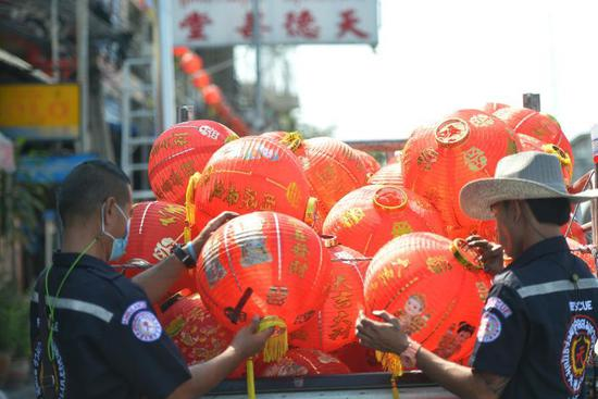 Staff members arrange lanterns to decorate street for upcoming Chinese Lunar New Year
