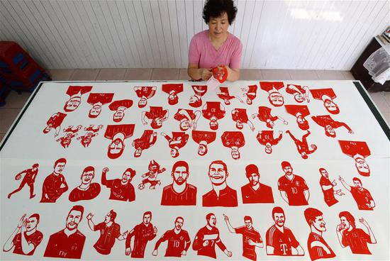 Craftswoman Feng Shiping makes paper-cutting works to greet the FIFA World Cup in Handan, north China's Hebei Province, June 12, 2018. (Xinhua/Hao Qunying)