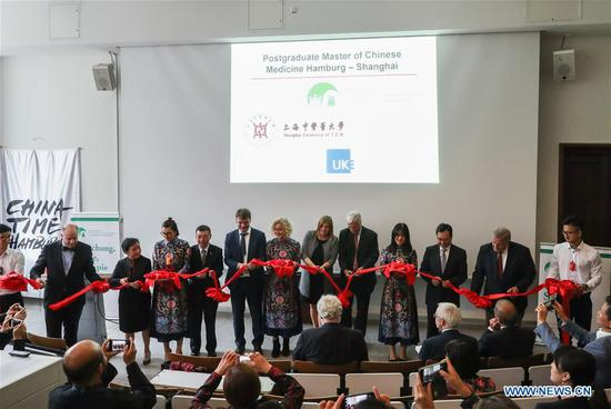 Guests cut the ribbon during the inauguration ceremony for the first German-Chinese joint master program in Traditional Chinese medicines (TCM) and a TCM exhibition, at the Museum of Medical History in Hamburg, northern Germany, on Sept. 12, 2018. The first German-Chinese joint master program in Traditional Chinese medicines (TCM) at a university hospital kicked off in Hamburg on Wednesday. (Xinhua/Shan Yuqi)