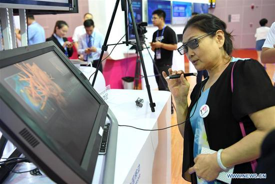 A visitor experiences a remote medical system at the 15th China-ASEAN Expo in Nanning City, south China's Guangxi Zhuang Autonomous Region, Sept. 13, 2018. High-tech exhibits attracted many visitors at the expo. (Xinhua/Zhou Hua)