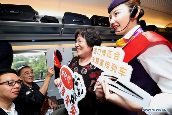 A railway attendant briefs passengers on information about the first China International Import Expo (CIIE) on board the G2 bullet train in east China's Shanghai, Oct. 10, 2018. Railway authorities have launched a campaign on Wednesday to promote the upcoming first CIIE on bullet trains running on the Beijing-Shanghai high-speed railway. (Xinhua/Chen Fei)
