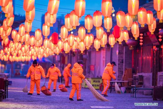 Sanitation workers clean a street in Hohhot, capital of north China's Inner Mongolia Autonomous Region, Feb. 4, 2019. People from various industries stick to their posts on the eve of the Spring Festival which falls on Feb. 5 this year. (Xinhua/Ding Genhou)