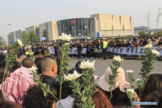 People mourn for Xu Penglong, Zhao Yongyi, Zhang Shuai and Kang Rongzhen, martyrs who died while fighting a forest fire in southwest China's Sichuan Province, as their remains are taken back to their hometown in Linyi, east China's Shandong Province, April 5, 2019. (Xinhua/Xu Chuanbao)