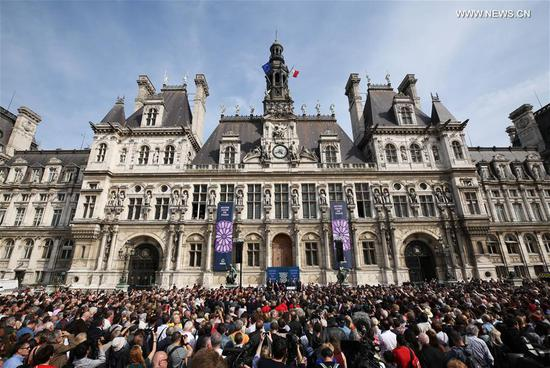 People participate in a commemoration ceremony for the cathedral of Notre Dame de Paris in front of the Hotel de Ville of Paris in Paris, France, April 18, 2019. A ceremony was held in front of Hotel de Ville of Paris on Thursday to commemorate the cathedral of Notre Dame de Paris which caught fire on Monday afternoon in Paris. (Xinhua/Gao Jing)