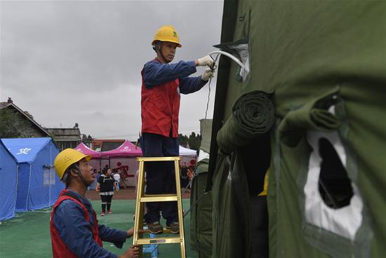 Electricians set up facilities at a make-shift shelter in Quanan Town of Neijiang City, southwest China's Sichuan Province, Sept. 8, 2019. The 5.4-magnitude earthquake in Sichuan Province had killed one person and left 63 others injured, three severely, as of 6 p.m. Sunday, local authorities said. (Xinhua/Liu Kun)