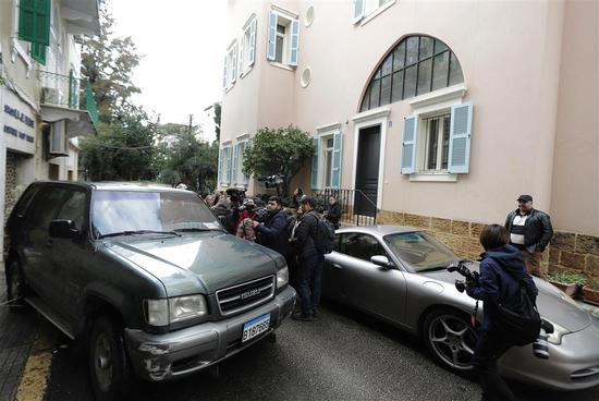 Journalists gather around an unidentified car outside a house referenced by court documents as belonging to former Nissan chief Carlos Ghosn in the capital Beirut on January 2.