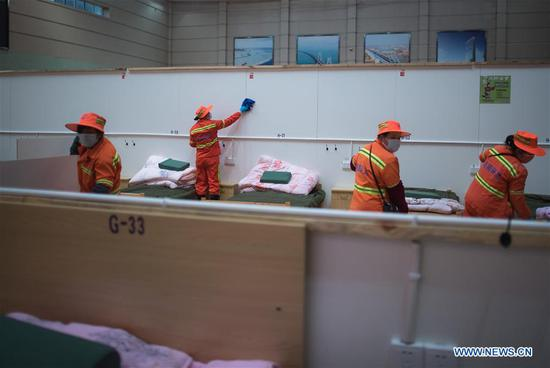 Workers clean a temporary hospital converted from Wuhan Sports Center in Wuhan, central 四不像心水's Hubei Province, Feb. 12, 2020. With the fundamental facilities being set up, the temporary hospital with a total of 1,100 beds is ready to admit patients with mild symptoms caused by the novel coronavirus. (Xinhua/Xiao Yijiu)