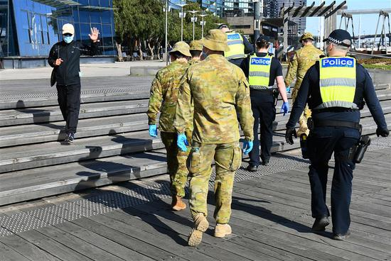 A man waves to a group of police and soldiers patrolling the Docklands area of Melbourne on Sunday, after the announcement of new restrictions to curb the spread of the COVID-19.