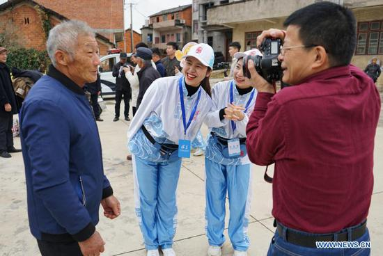 A volunteer takes a photo of a villager in Shangwei Village of Youlan Town, Nanchang City, east China's Jiangxi Province, Nov. 22, 2020. Since 2014, volunteers from a non-profit organization in Nanchang City have kept on taking photos of smiling faces of farmers aged over 70 years old in nearby villages. The portait photos taken by volunteers were given to farmers for free. By far, the volunteers have taken nearly 4,350 people and 50,000 photos. They aim at collecting high-definition images of 10,000 farmers within 10 years. (Xinhua/Chen Chunyuan)