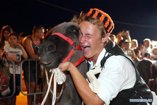A rider poses with his donkey during the 51st traditional donkey races in Tribunj, Croatia, on Aug. 1, 2018. The event which dates back to 1950s features donkey-riders in traditional costumes racing around the village of Tribunj. (Xinhua/Dusko Jaramaz)