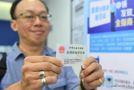 A Taiwan resident living in the Chinese mainland displays the residence permit at Nanjie police station of Gulou Branch of Fuzhou Municipal Public Security Bureau in Fuzhou, southeast China's Fujian Province, Sept. 3, 2018. A new regulation on the application and granting of residence permits for Hong Kong, Macao, and Taiwan residents living in the Chinese mainland was put into effect on Sept. 1. (Xinhua/Lin Shanchuan)
