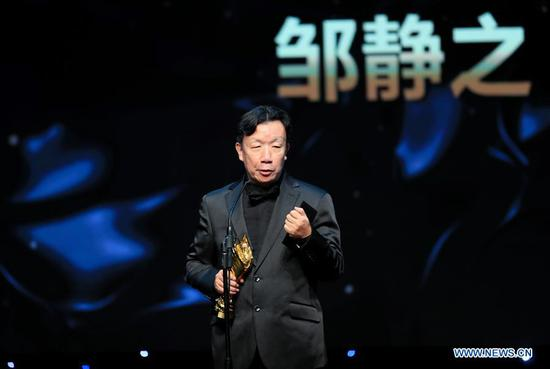 Writer Zou Jingzhi who won the Outstanding Achievement Award, receives the trophy during the awarding ceremony of the 14th Chinese American Film Festival (CAFF) in Los Angeles, the United States, Oct. 30, 2018. The 14th Chinese American Film Festival (CAFF) kicked off Tuesday at the Ricardo Montalban Theater in Hollywood in the U.S. city of Los Angeles. (Xinhua/Li Ying)