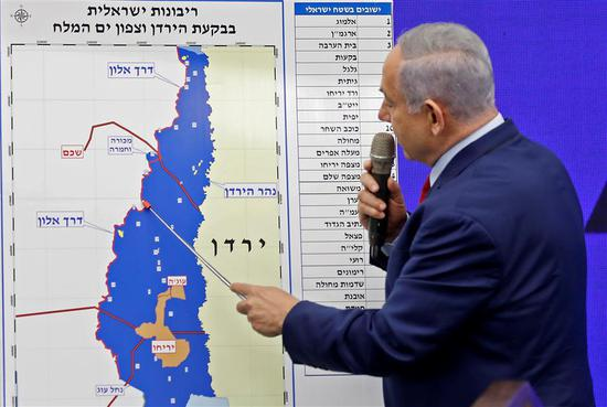 Israeli Prime Minister Benjamin Netanyahu points at a map of the Jordan Valley as he gives a statement in Ramat Gan, near the Israeli coastal city of Tel Aviv, on September 10, 2019.
