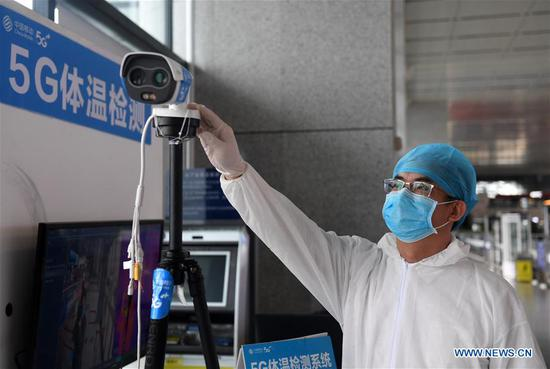 A staff member adjusts a device of a 5G body temperature screening system at Nanning East Railway Station in Nanning City, south China's Guangxi Zhuang Autonomous Region, Feb. 13, 2020. The 5G body temperature screening system, which is able to automatically check passengers' body temperature and issue warnings, has been put into use in Nanning East Railway Station to help fight the novel coronavirus epidemic. (Xinhua/Lu Boan)