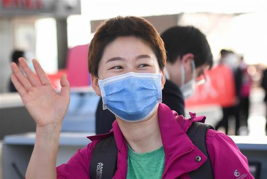 A medical staffer from northwest China's Xinjiang Uygur Autonomous Region waves goodbye to people seeing them off at the Wuhan Tianhe International Airport, in Wuhan, central China's Hubei Province, March 17, 2020. Some medical assistance teams started leaving Hubei Province on Tuesday as the epidemic outbreak in the hard-hit province has been subdued. (Xinhua/Chen Yehua)