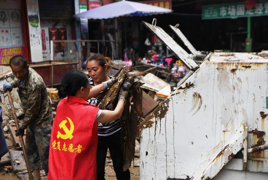 People clean a street at a market in Ganshui Township of Qijiang District, southwest China's Chongqing, June 23, 2020. (Xinhua/Wang Quanchao)