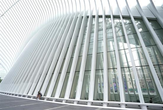 A man sits outside the World Trade Center Transportation Hub's Oculus in New York on September 9, 2020.