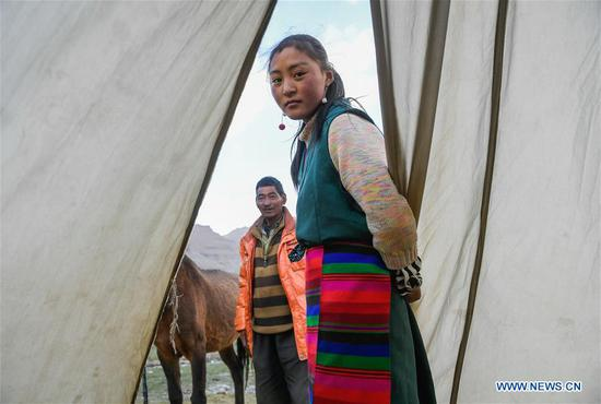 A girl (R) from Gangsha Village rests at a tent in Ali Prefecture, southwest China's Tibet Autonomous Region, June 25, 2018. Gangsha Village is located at the foot of Mount Kangrinboqe, a sacred Hindu and Buddhist site in Ali. Since the 1980s, local farmers and herdsmen have started to receive pilgrims and tourists from home and abroad. They upgraded services of tourism industry in the past 30 years, and tourism increased villagers' income. (Xinhua/Liu Dongjun)