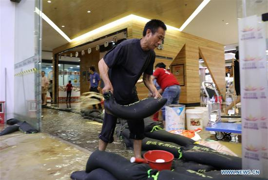 A staff of a shop carries a sand bag to keep away flood water in Haikou, south China's Hainan Province, Aug. 10, 2018. Hainan was hit by heavy rainfalls under the influence of a tropical depression on Friday, which triggered a red alert for rainstorms in seven cities and counties, including Haikou. (Xinhua/Wang Junfeng)