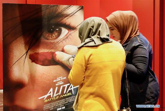 Photo taken on Feb. 21, 2019 shows two Iraqi women beside a movie poster at a movie theater in Baghdad, Iraq. (Xinhua/Khalil Dawood)