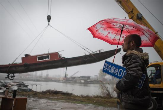 A former fisherman Xia Mingxin holding his boat license plate watches his trawler being hauled out to be destroyed at the Yangtze Finless Porpoise National Nature Reserve in Hubei Province on December 25, 2019.