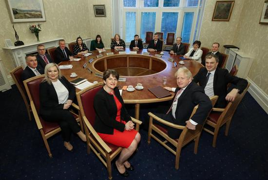 Britain's Prime Minister Boris Johnson (fourth right) and Britain's Northern Ireland Secretary Julian Smith (second right) pose for a photograph with Northern Ireland's First Minister Arlene Foster (front row center) and Deputy First Minister Michelle O'Neill (third left), along with other members of the Norhtern Ireland Assembly, on the Stormont Estate in Belfast on January 13, 2020.