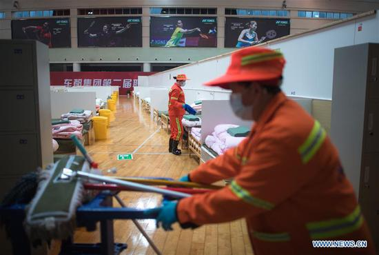 Workers do preparation work at a temporary hospital converted from Wuhan Sports Center in Wuhan, central China's Hubei Province, Feb. 12, 2020. With the fundamental facilities being set up, the temporary hospital with a total of 1,100 beds is ready to admit patients with mild symptoms caused by the novel coronavirus. (Xinhua/Xiao Yijiu)