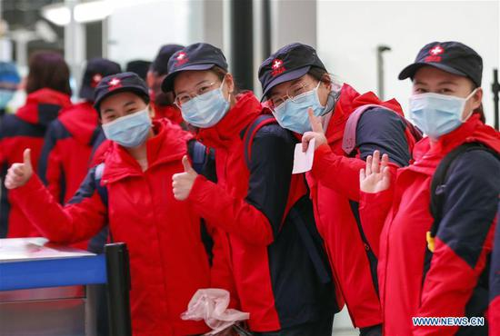 Medical team members pose for a group photo before leaving for Hubei Province at Chongqing Jiangbei International Airport in southwest China's Chongqing, Feb. 15, 2020. The ninth batch of 100 medical workers from Chongqing left for Hubei Province on Saturday to aid the novel coronavirus control efforts there. (Photo by Huang Wei/Xinhua)