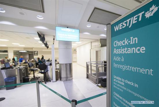 Travellers check in at the WestJet check-in counter of Pearson International Airport in Toronto, Canada, March 24, 2020. Canada's second largest airline WestJet on Tuesday announced to lay off 6,900 employees due to the impact of the COVID-19 pandemic. Nearly two-thirds of the airline's fleet of 120 aircrafts are currently grounded. (Photo by Zou Zheng/Xinhua)