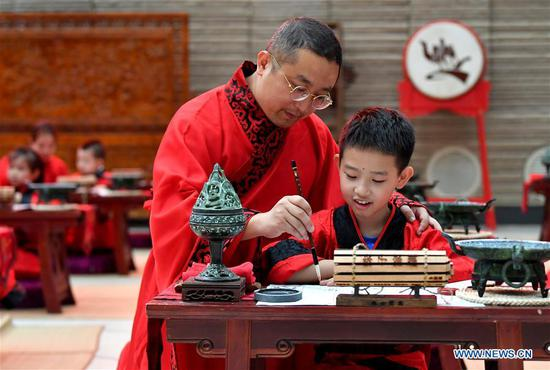 A boy and his parent attend the First Writing Ceremony, a traditional activity held for children before they are admitted to school, at a museum in Xi'an, northwest China's Shaanxi Province, Sept. 13, 2020. (Xinhua/Liu Xiao)
