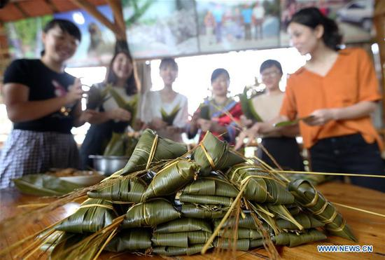 Visitors and residents make colorful Zongzi, pyramid-shaped dumplings made of glutinous rice wrapped in bamboo or reed leaves, to greet the upcoming Dragon Boat Festival in Rong'an County, south China's Guangxi Zhuang Autonomous Region, June 12, 2018. (Xinhua/Tan Qinghe)