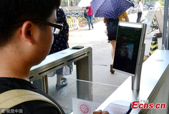 A student undergoes a facial recognition test before entering a school gate at Peking University in Beijing, July 3, 2018. Peking University is the first in China to adopt such a more powerful facial recognition system, capable of accurately and efficiently comparing one person's facial data with the information of many others. (Photo/VCG)